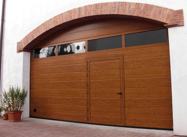 Portone sezionale Breda® in tinta legno con oblò e porta pedonale inserita, montato su foro a sesto ribassato.